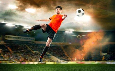 Photo pour Footballeur en chemise orange frappant le ballon au stade - image libre de droit