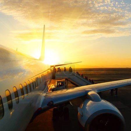 Photo pour Avion à l'aéroport au coucher du soleil - image libre de droit