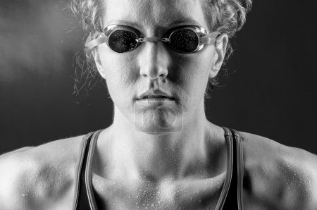 Photo for Portrait of a looking at camera strong muscular woman swimmer, blue toned on blue background - Royalty Free Image