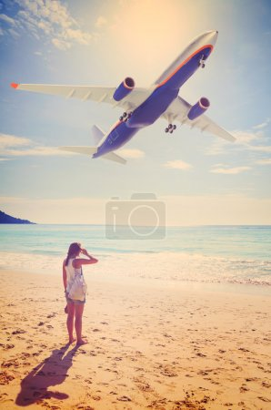 Photo for Summer travel. young woman is standing on beach with aeroplane flying above - Royalty Free Image