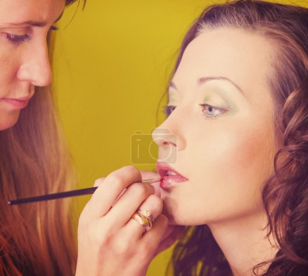 Photo for Makeup artist is applying cosmetics on model face - Royalty Free Image