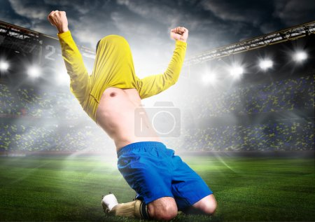 Photo for Soccer or football player is celebrating goal on stadium with his jersey on head - Royalty Free Image