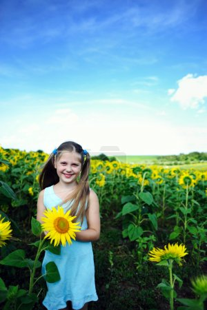 Photo for An image of a happy girl with a sunflower - Royalty Free Image