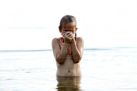 A little girl in a swimsuit standing in water up to his waist and rubbed his eyes from the trapped water