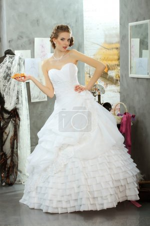 Girl in a wedding dress makes fitting in the clothing design studio