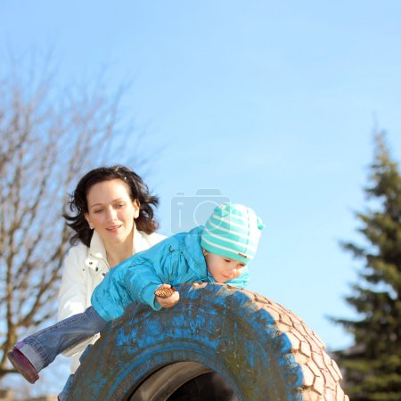 Beautiful young mother doing fitness with his little daughter at the playground