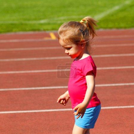 Little girl running at the stadium