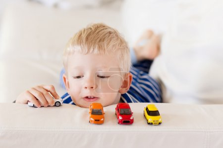 Toddler plays toy cars