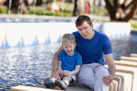 Photo pour Famille de deux jouissant du temps ensemble à l'extérieur, jeune beau père et son adorable fils riant les yeux fermés près de la fontaine - image libre de droit