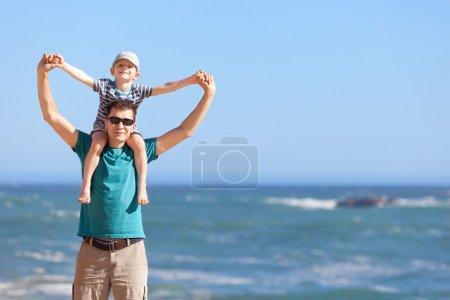 Photo pour Beau père souriant et son fils heureux assis sur les épaules tenant la main à la plage - image libre de droit