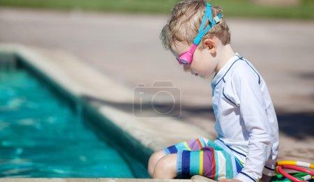 Foto de Lindo niño concentrarse antes de entrenamiento de natación - Imagen libre de derechos
