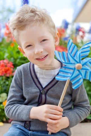 Photo for Cute smiling little boy holding pinwheel and having fun at summer - Royalty Free Image