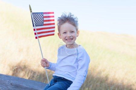 Photo pour Mignon petit garçon tenant le drapeau américain et à célébrer la fête de l'indépendance - image libre de droit