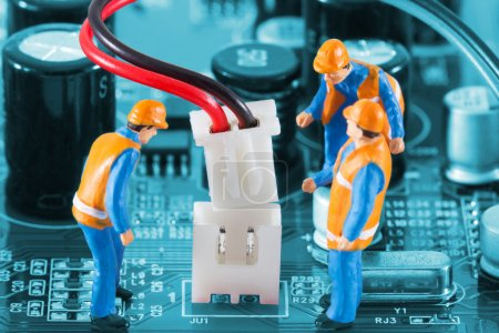 Photo for Miniature engineers fixing wire connector of circuit board. Computer repair concept. Close-up view. - Royalty Free Image