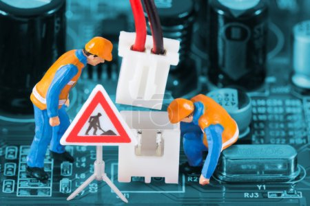 Photo for Miniature engineers fixing wire connector on circuit board. Computer repair concept. Close-up view. - Royalty Free Image