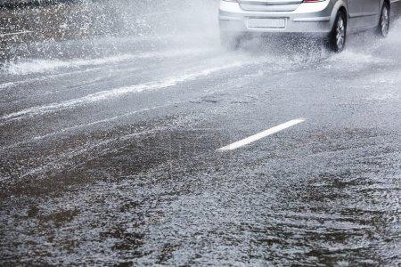 Photo pour Voiture conduite dans la rue de la ville après de fortes pluies - image libre de droit