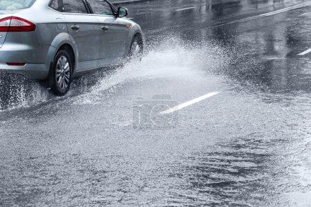 Photo pour Voiture conduite sur une énorme flaque d'eau lors d'une averse - image libre de droit