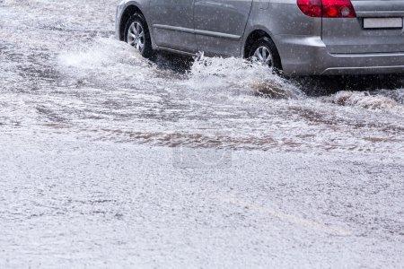 Photo pour Voiture traversant une inondation éclair sur la route - image libre de droit