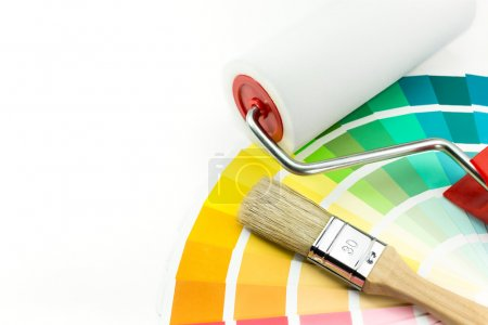 Paint roller and brush over color swatches