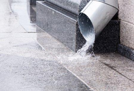 Photo pour L'eau de pluie s'écoule d'une trombe pendant un orage - image libre de droit
