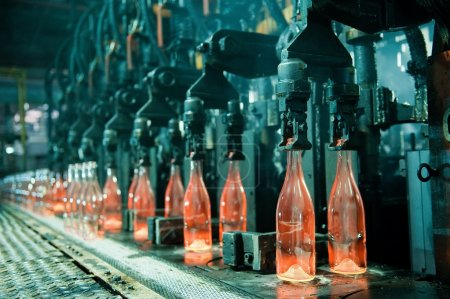 Photo for Row of hot orange glass bottles in factory - Royalty Free Image