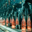 Row of hot orange glass bottles in factory...