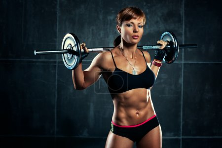 Photo for Young sports woman with barbell. - Royalty Free Image