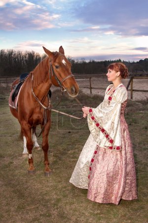 beautiful girl in antique dress next to a horse