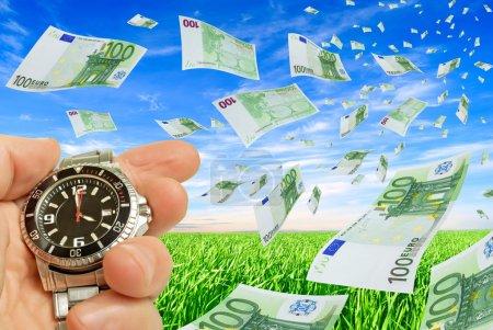 Photo pour Collage avec des volants euro horloge dans une main sur un fond de ciel et l'herbe. - image libre de droit