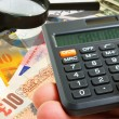A hand with a calculator against various bills and...