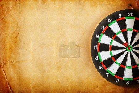 Vintage dart board on dark wall grunge