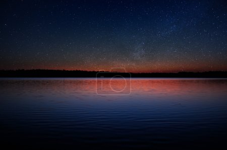 Photo for A beautiful sunset over a calm lake with a black forest on the horizon and real stars in the sky - Royalty Free Image