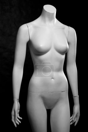 Old female fashion mannequin on a black background