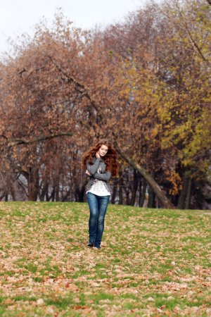 Photo for Walking woman in autumn park - Royalty Free Image