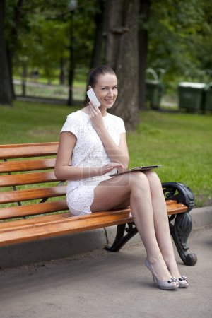 Brunette sitting on a bench in a summer park