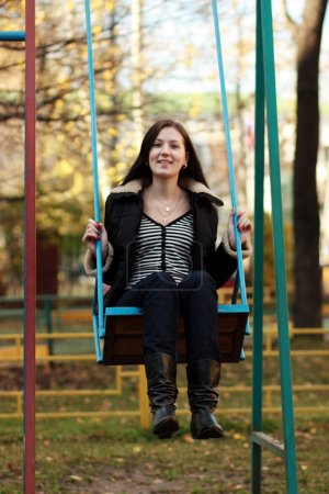 Young woman wearing sitting on a swing in a park