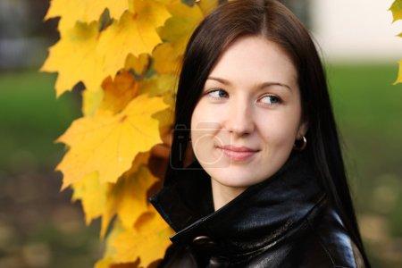 Beautiful brunette woman with golden autumn leaf