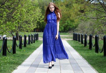 Photo pour Jeune belle fille en robe bleue de marche dans le parc de l'été - image libre de droit