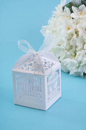 Pretty present box and wedding bouquet isolated on blue background