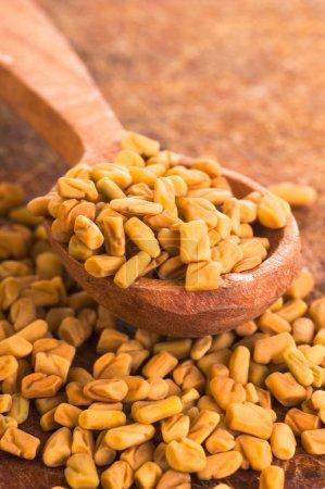 Fenugreek Seeds in wooden spoon on wooden backgrou...