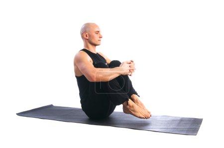 Man in balance yoga pose ubhaya padasana