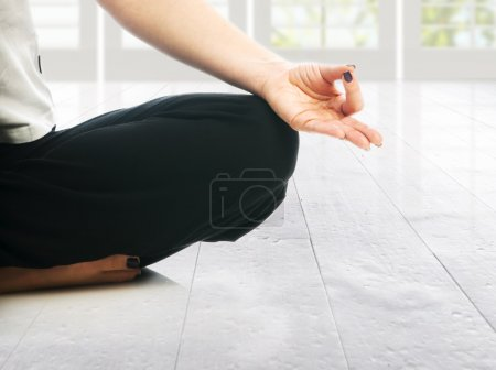 Woman in lotus position making ohm mudra gesture