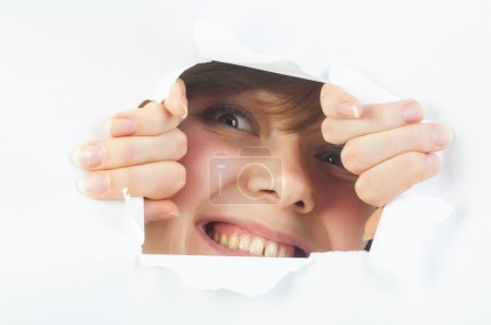Smiling woman looking through hole in paper