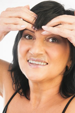 Mature woman massaging her forehead
