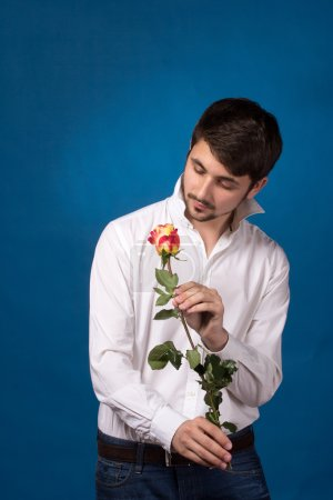 Young man looking to red rose