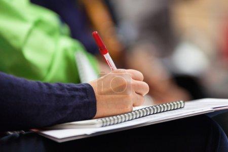 Photo pour Gros plan des mains tenant des stylos et prenant des notes lors de la conférence - image libre de droit