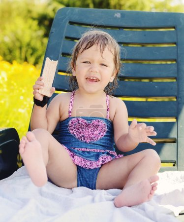Photo for Cute toddler girl sitting on sun lounger and eating crisp bread - Royalty Free Image