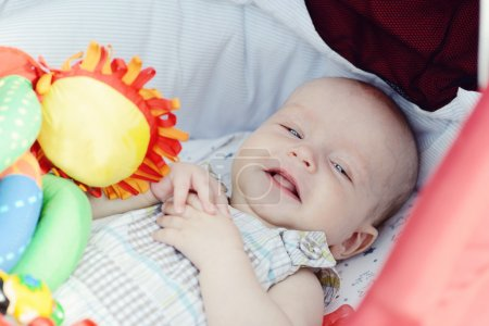 Photo pour Heureux bébé garçon étendu dans landau - image libre de droit