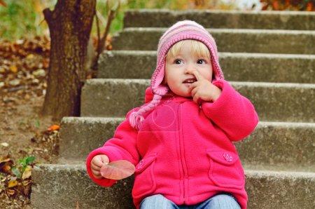Photo pour Bébé fille cueillette son nez à l'extérieur - image libre de droit
