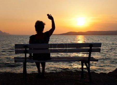 Photo pour Femme sur le banc et le coucher du soleil - fond de vacances - image libre de droit